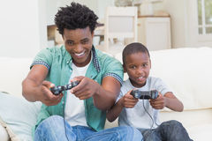 Father and son playing video games together. At home in the living room royalty free stock photo