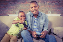 Father and son playing video games together Stock Photos
