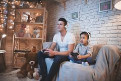 Father and son are playing video games on tv at night at home. Father and son are playing video games on tv on couch at night at home royalty free stock photos