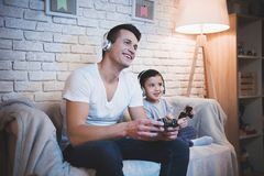 Father and son are playing video games on tv at night at home. Father and son are playing video games on tv on couch at night at home stock images