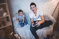 Father and son are playing video games on tv at night at home. Father and son are playing video games on tv on couch at night at home stock photography