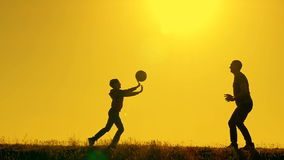 Father and son playing volleyball in the park at sunset, silhouettes against the backdrop of a bright sun stock video footage