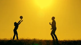 Father and son playing volleyball in the park at sunset, silhouettes against the backdrop of a bright sun stock video