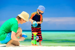 Father and son playing with water on beach Stock Images