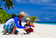 Father and son playing with water guns on the beach Royalty Free Stock Images