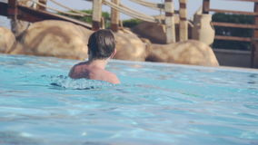 Father and son playing water polo in swimming pool stock video