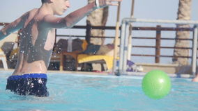 Father and son playing water polo in swimming pool stock footage