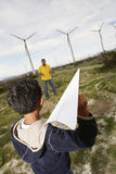 Father And Son Playing At Wind Farm. Father and son playing with paper plane at wind farm Royalty Free Stock Images