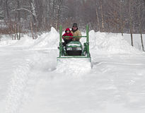 Father and son plow a snowy drive on a tractor Royalty Free Stock Photography