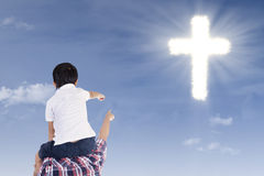 Father and son pointing at cross. On the blue sky Stock Images