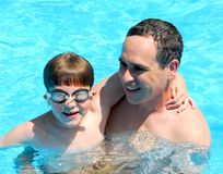 Father son pool. Father and son having fun in a swimming pool Royalty Free Stock Image