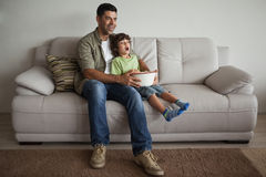 Father and son with popcorn bowl watching tv in the living room Stock Photography