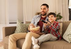 Father and son with popcorn watching tv at home. Family, childhood, fatherhood, technology and people concept - happy father and little son with popcorn and royalty free stock photos
