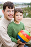 Father and son. Portrait of father embracing his son holding ball Stock Photo