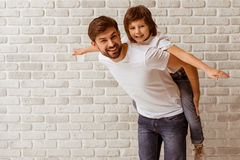 Father and son. Portrait of a handsome father carrying his cute son on back. Both in white t-shirts smiling, standing against white brick wall Royalty Free Stock Images