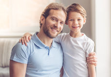 Father and son. Portrait of father and son hugging, looking at camera and smiling while standing in the living room royalty free stock image