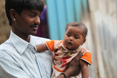 Father and Son. A portrait of a poor Indian father holding his little son, looking at him lovingly Royalty Free Stock Images