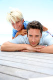 Father and son portrait. Young boy laying over his dad's back by pool royalty free stock images