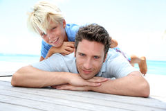Father and son portrait. Young boy laying over his dad's back by pool stock photo