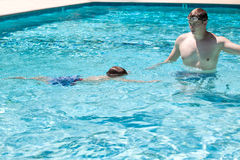 Father and son practicing in the pool Royalty Free Stock Image