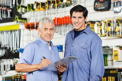 Father And Son Preparing Checklist In Hardware Stock Photos