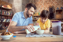 Father and son preparing chocolate corn balls with milk Stock Image