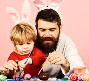 Father and son preparing for holiday. Easter celebration. And joy concept. Dad with painted nose wears bunny ears. Man with beard and little boy painting eggs royalty free stock image