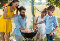 Father and son preparing meat on charcoal barbecue grill during Royalty Free Stock Photo