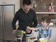 Father And Son Preparing Salad At Kitchen Counter Stock Images