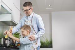 Father and son preparing spaghetti in kitchen Stock Photos