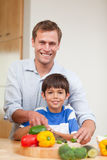 Father and son preparing vegetables Royalty Free Stock Photos