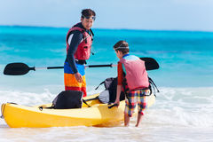 Father and son pulling kayak Royalty Free Stock Photography