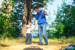 Father and son put a tent. In the camping Royalty Free Stock Photo