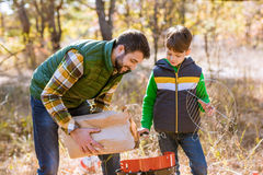 Father and son putting coals in grill royalty free stock photo
