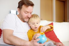 Father and son putting coin into piggy bank. Education of children in financial literacy royalty free stock photography