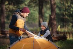 father and son putting up tent stock photography