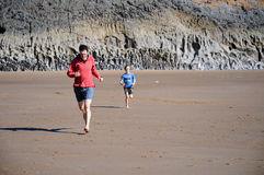 Father and son racing on the beach. Action shot of father and son racing on beach royalty free stock image