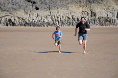 Father and son racing on the beach. Action shot of father and son racing on beach stock photography