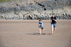Father and son racing on the beach. Action shot of father and son racing on beach royalty free stock photography