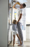 Father And Son Raiding The Fridge For Drink Stock Photography