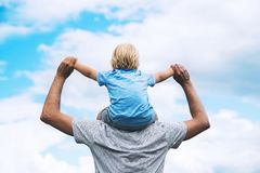 Father and son with raised arms up against the sky. Father carrying his son on his back with raised arms up against the sky. Man and child boy. Family Royalty Free Stock Photo