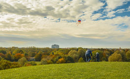 Father and son raising a kite on the cloudy sky royalty free stock photo