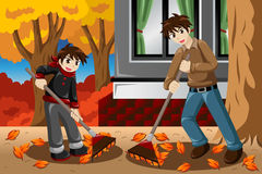 Father son raking leaves during Fall season Stock Photography