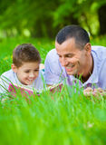 Father and son read book in park. Father and son read book lying on green grass in park. Concept of happy family relations and carefree leisure time Royalty Free Stock Photo