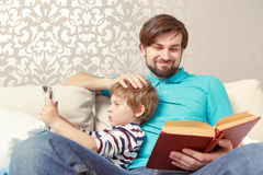 Father and son read a book or tablet Stock Images
