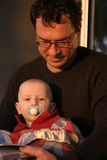 Father and son reading. Father and infant son reading outside in early morning sun royalty free stock photos
