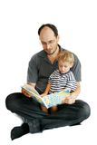Father and son reading book stock images