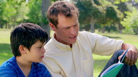Father and son reading a book aloud. In the countryside stock footage