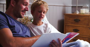Father And Son Reading Book In Bed Together stock video footage