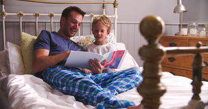 Father And Son Reading Book In Bed Together
